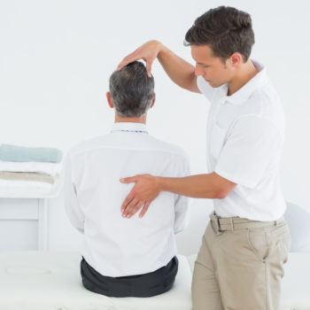 Rear view of a male chiropractor examining mature man at office
